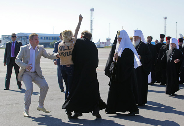 An activist from Ukrainian women's rights group FEMEN performs an act of protest against the Russian Orthodox Patriarch Kirill upon his arrival at the Kiev airport on July 26, 2012. Source: AFP / East News