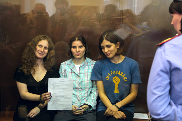 Feminist punk group Pussy Riot members, from left, Maria Alekhina, Yekaterina Samutsevich, and Nadezhda Tolokonnikova show the court's verdict as they sit in a glass cage at a court room in Moscow on Friday, Aug 17, 2012. A judge found three members of the provocative punk band Pussy Riot guilty of hooliganism on Friday, in a case that has drawn widespread international condemnation as an emblem of Russia's intolerance of dissent. Source: AP Photo/Mikhail Metzel