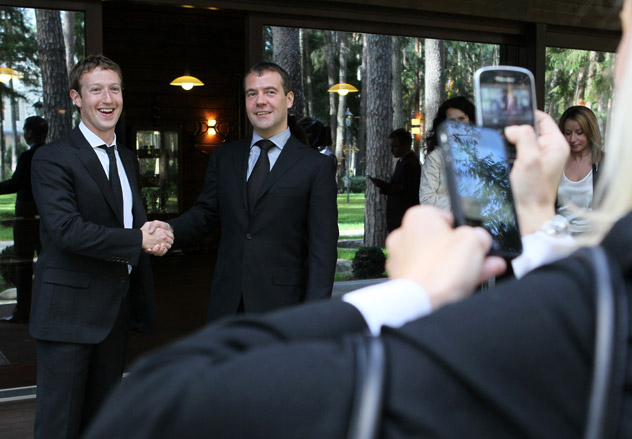 A blonde woman taking pictures with an iPhone of Prime Minister of Russia Dmitry Medvedev (R) and Facebook's founder, Mark Zuckerberg, during their meeting. Source: ITAR-TASS.
