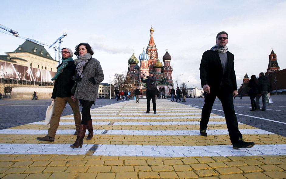 People walk along a road surface marking which is painted on the stone-block pavement of Red Square, with St. Basil's Cathedral and the Kremlin wall (R) seen in the background, in central Moscow April 17, 2015.