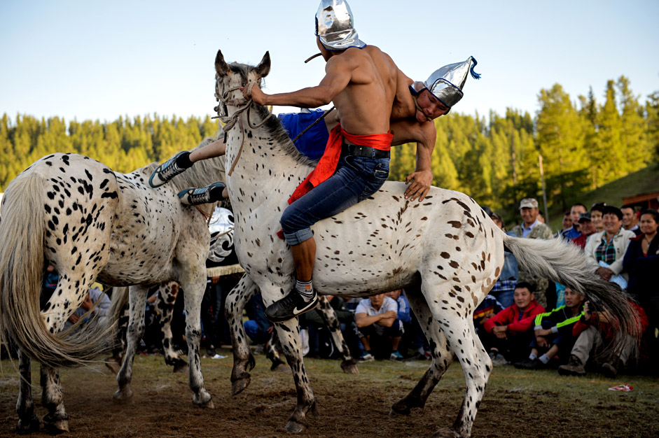Two Telengits horseback wrestlers take each other on as part of a celebration of the 150th anniversary of the unification of the Telengits people and Russia on June 19