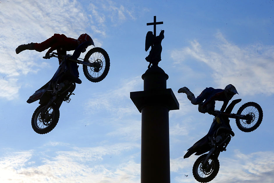 Bikers perform spectacular jumps in front of Alexander Column duringthe 'Adrenaline FMX Riders Motofreestyle-battle' at the Palace(Dvortsovaya) Square in St. Petersburg, Russia