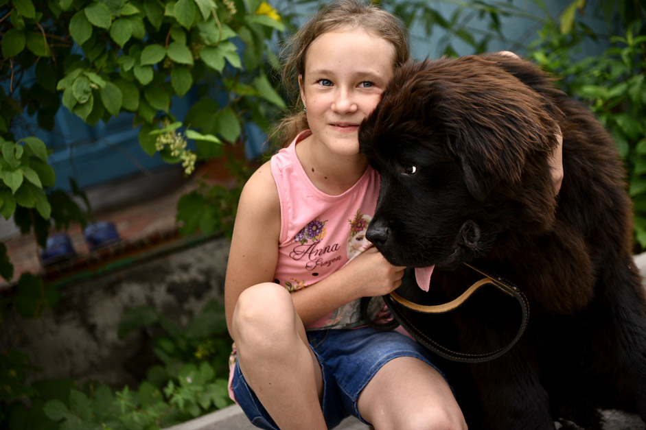 Dasha Yaitskaya, a citizen of Kyrygzstan, with a Newfoundland puppy, a gift from Russian President Vladimir Putin, on July 23 2015. Yaitskaya wrote an email to Putin's 'Direct Line' live TV call-in show in spring, asking for a dog.