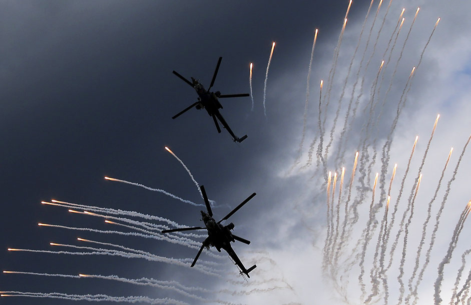 "A Mi-28N (top) from the Berkuty (Golden Eagles) helicopter display team flies in formation during a performance before its hard touchdown at the ""Aviadarts"" military aviation competition at the Dubrovichi range near Ryazan, Russia, August 2, 2015."