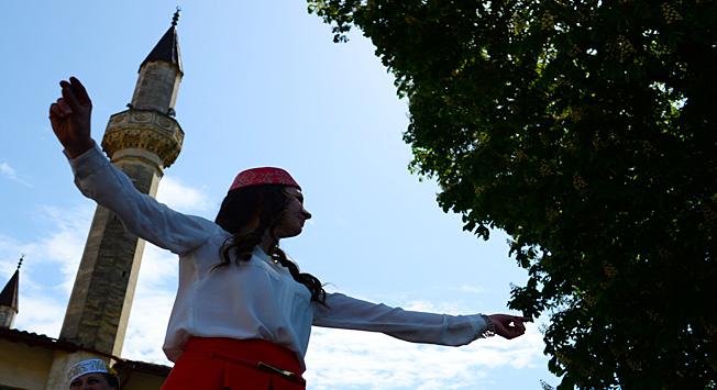Seorang perempuan muda menampilkan tarian tradisional Tatar Krimea di halaman Istana Khan di Bakhchysarai.