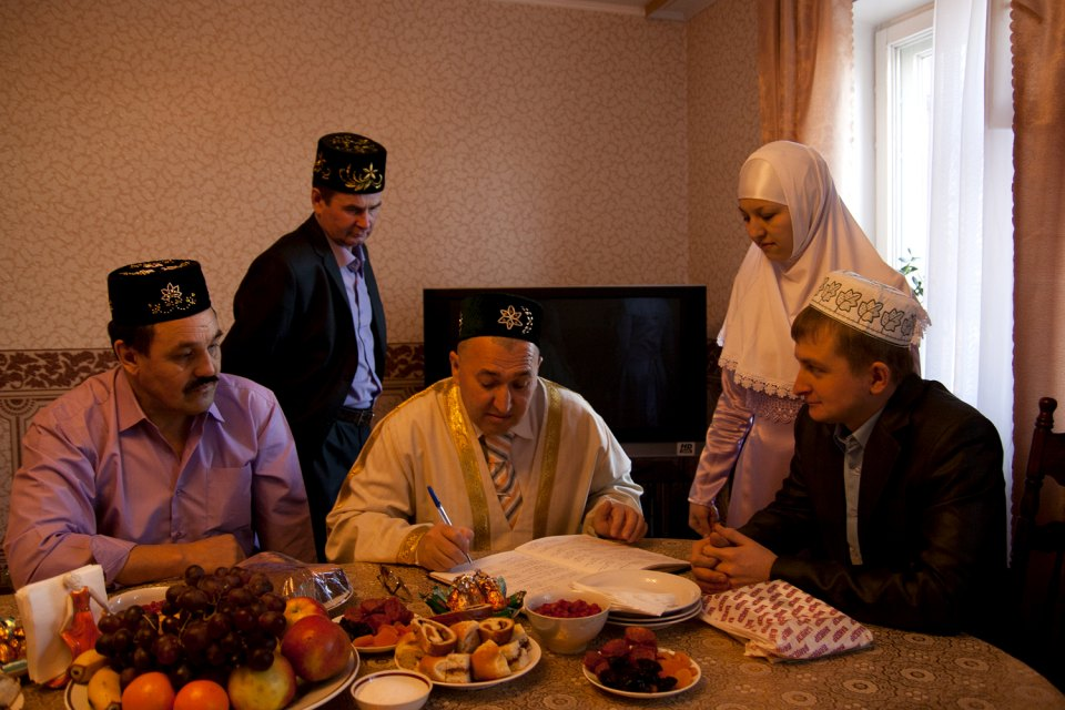 Imam menggelar upacara pernikahan. Pengantin perempuan dan pengantin pria berada di sebelah kanan.