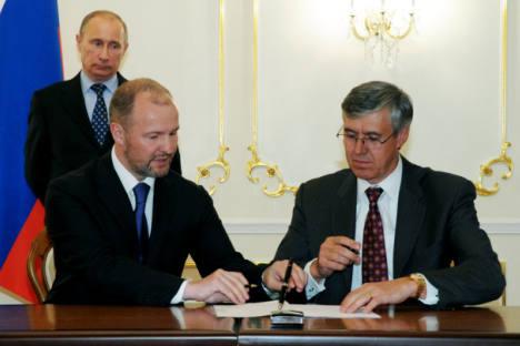 Premiê russo Vladímir Pútin (em segundo plano) durante cerimônia de assinatura de acordos realizada na residência de Novo-Ogariovo. Da esquerda à direita (em primeiro plano), estão os presidentes da United Shipbuilding Corporation, Roman Trotsênko, e