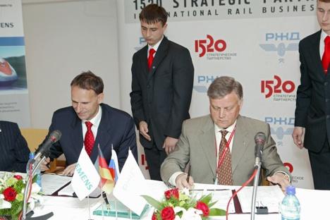 Der eine lächelt, der andere nicht: Siemens-Transportation-Group-Präsident Hans Schabert und Chef der Russischen Eisenbahn Boris Jakunin unterzeichnen Abkommen. Foto: Kommersant