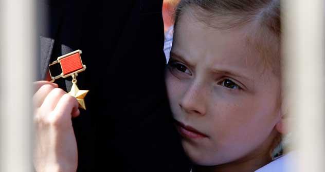 """Verbundenheit der Generationen: Die Enkelin eines Veteranen umarmt ihren Großvater und zupft an seinem """"Held der Sowjetunion""""-Orden, der einst höchsten Auszeichnung des Landes. Foto: AFP/Eastnews"""