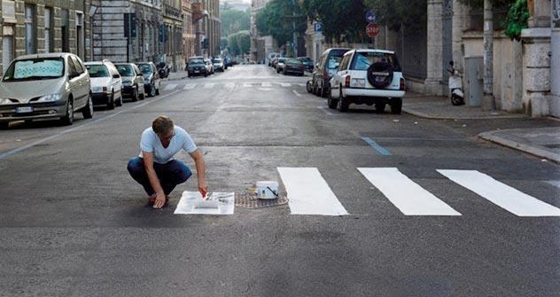 """Ein Aktivist der """"Partisaning""""-Bewegung bringt einen Zebrastreifen auf den Fußgängerüberweg an. Foto: Didier Courbot"""