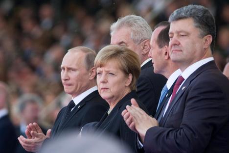 Wenn auch gegen den Willen haben sich Wladimir Putin, Angela Merkel und Petro Poroschenko beim D-Day-Feier in der Normandie endlich getroffen. Foto: Photoshot/Vostock-Photo