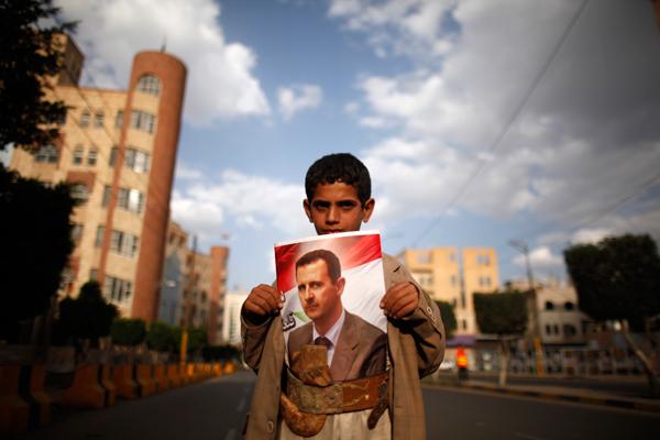 Seorang anak Suriah sedang memegang foto Presiden Bashar Assad di Sanaa.