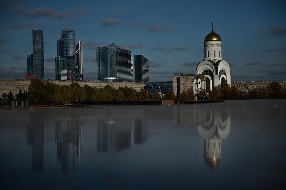 Die Kirche St. Georg auf dem Poklonnaja-Hügel in Moskau. Im Hintergrund sind die Wolkenkratzer des Finanzviertels Moskau City zu sehen.
