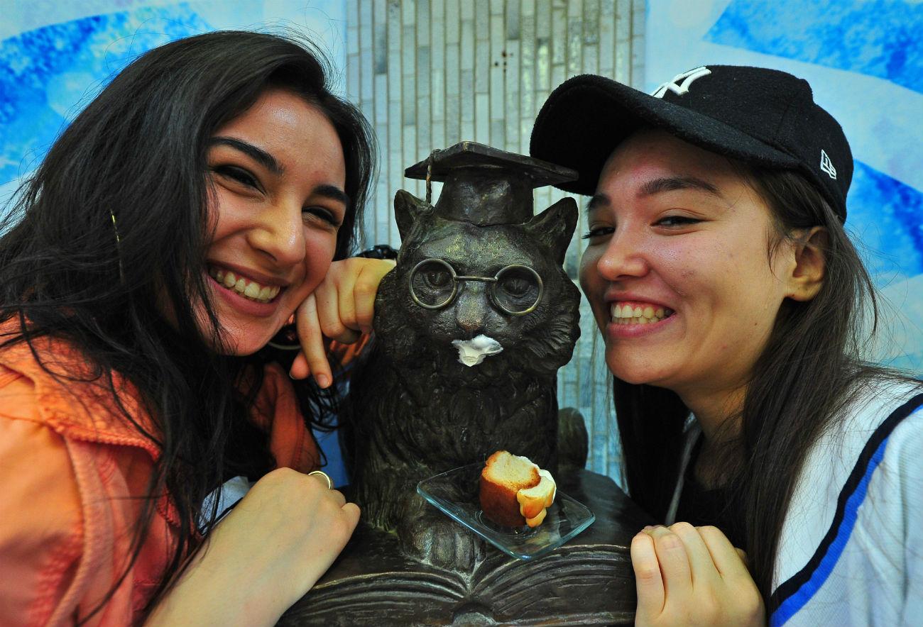 """Studentinnen der Russischen Universität der Völkerfreundschaft posieren vor dem Denkmal des klugen Katers, das am 25. Januar 2016 eingeweiht wurde. Die Figur stammt aus Puschkins Verserzählung """"Ruslan und Ljudmila""""."""