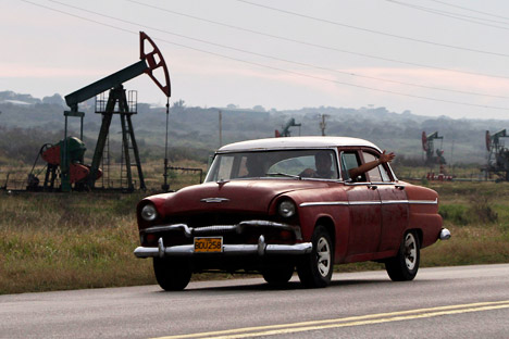 Russia will invest in a number of Cuban energy projects. Pictured: A man waving from his classic car as he drives by oscillating oil pumps operated by the state oil company Cuba Petroleos, Cupet, in Santa Cruz del Norte, Cuba. Source: AP