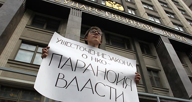 "An opposition activist protesting against the NGO bill in front of Russia's State Duma. The slogan reads ""The restrictions of the NGO bill is the authorities' paranoia."" Source: RIA Novosti / Evgeny Biyatov"