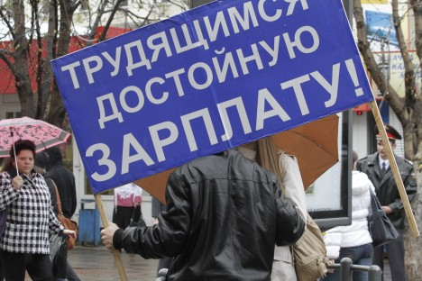 "Russian trade unions criticize the country's  pension system and reform of the Labor Code. Pictured: A participant of a rally with the motto which reads: ""Good Wage for Workers!""  Source: ITAR-TASS"
