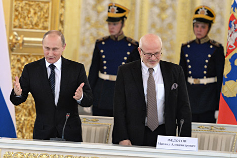 Russian President Vladimir Putin (left) and Chairman of Human Rights Council Mikhail Fedotov (right) greeting human rights activists. Source: Kommersant