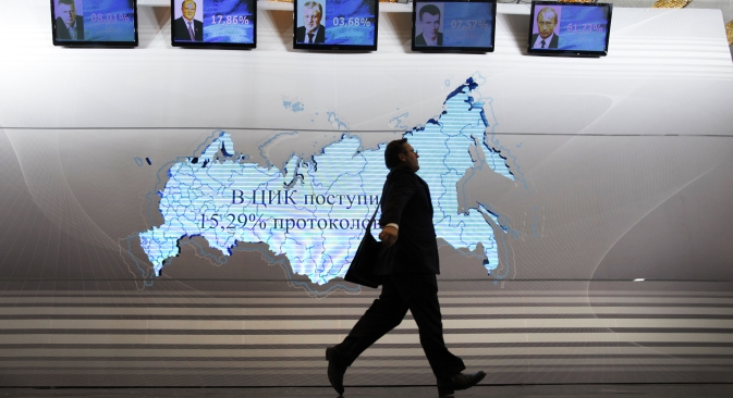 A man walks past a map of Russia and portraits of presidential candidates (L-R) Vladimir Zhirinovsky, Gennady Zyuganov, Sergei Mironov, Mikhail Prokhorov and Vladimir Putin at the Putin's headquarters in Moscow on March 4, 2012. Source: AP