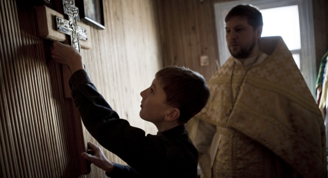 There is a simple greatness of daily life which can only be revealed far from big cities. Pictured: Fyodor helps to his father - Orthodox priest Roman - during the Sunday Service. Bagan Village, Novosibirsk Region, 2011. Source: Valery Klamm