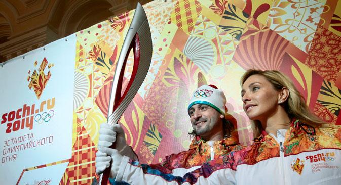Eistänzer Tatjana Nawka und Ilja Awerbuch präsentieren die  Fackel der olympischen Winterspielen in Sotschi. Foto: AP
