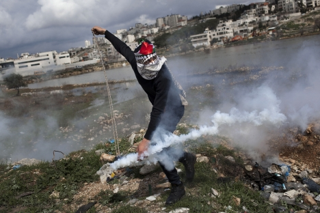 A Palestinian throws back a gas canister previously shoot by Israeli forces, not pictured, during a protest to support Palestinian prisoners, outside Ofer, an Israeli military prison near the West Bank city of Ramallah on Feb.19. Source: AP
