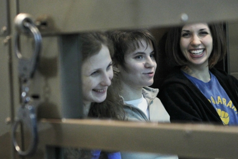 "Members of the female punk band ""Pussy Riot"" (L-R) Maria Alyokhina, Yekaterina Samutsevich and Nadezhda Tolokonnikova sit in a glass-walled cage before a court hearing in Moscow, October 1, 2012. Source: Reuters"
