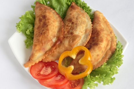 Cheburek is a fried turnover with a filling of ground or minced meat and onions. It is made with a single round piece of dough folded over the filling in a half-moon shape. Source: Lori / Legion Media