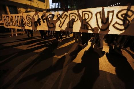 """Manifestantes anti-Troika seguram faixa com os dizeres """"Tirem as mãos do Chipre"""" durante protesto na frente do escritório da UE, em Nicósia Foto: Reuters"""