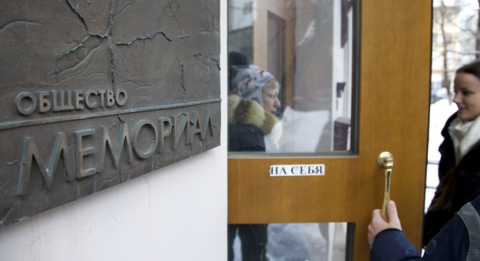 People talk near the entrance to human rights group Memorial's office, in Moscow, Russia, on Thursday, March 21, 2013, as prosecutors search for documents pertaining to all of its activities. Source: AP