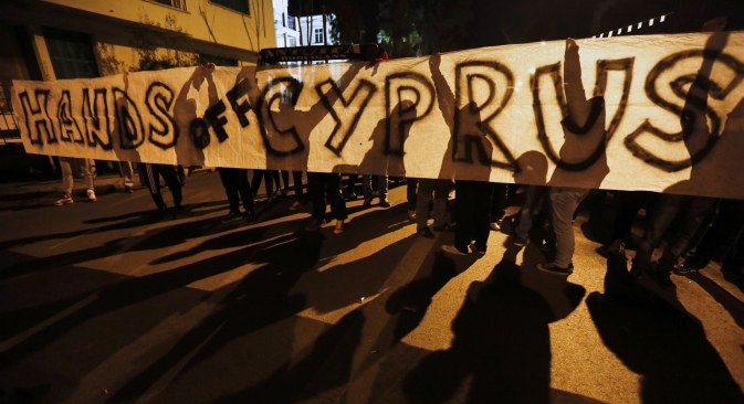 "Anti-Troika protesters hold a ""Hands off Cyprus"" banner during a demonstration outside the EU offices in Nicosia on March 24. Source: Reuters"