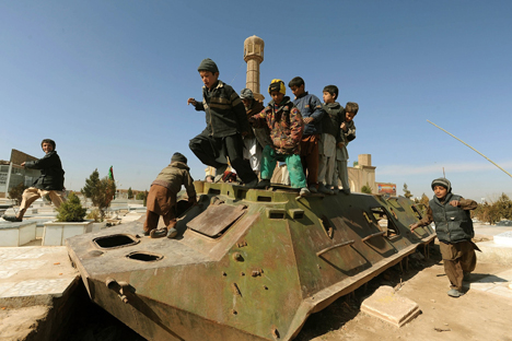 Afghan children play on the remains of a Soviet-era armoured personnel carrier in Herat on February 15, 2012. Source: AFP / East News