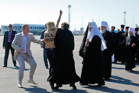 An activist from Ukrainian women's rights group FEMEN performs an act of protest against the Russian Orthodox Patriarch Kirill upon his arrival at the Kiev airport on July 26, 2012. Source: AFP