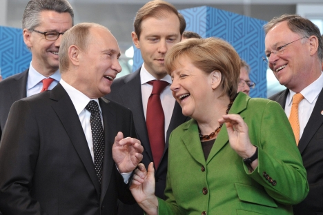 German Chancellor Angela Merkel, right, and Russian President Vladimir Putin, left, laugh as they open Hanover Fair, in Hannover, central Germany, on Monday, April 8, 2013. Source: AP