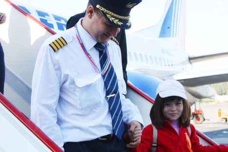Stepping out: Pilot Evgeny Bogach gives a young patient a taste of the high life. Source: Transaero