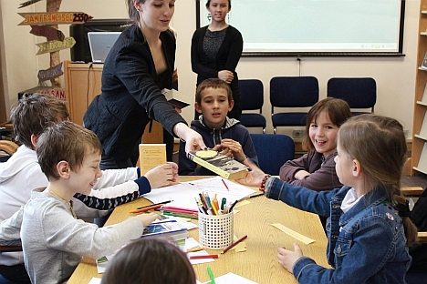 Global UGRAD alumna Ekaterina Pshenitsyna giving a small present to the most active participants of the AMC Teenagers' Club. Source: RBTH / Pavel Koshkin
