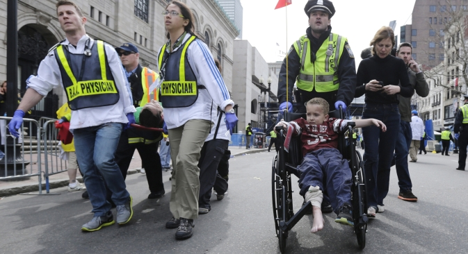 A Boston police officer wheels in injured boy down Boylston Street as medical workers carry an injured runner following an explosion during the 2013 Boston Marathon in Boston, Monday, April 15, 2013. Source: AP