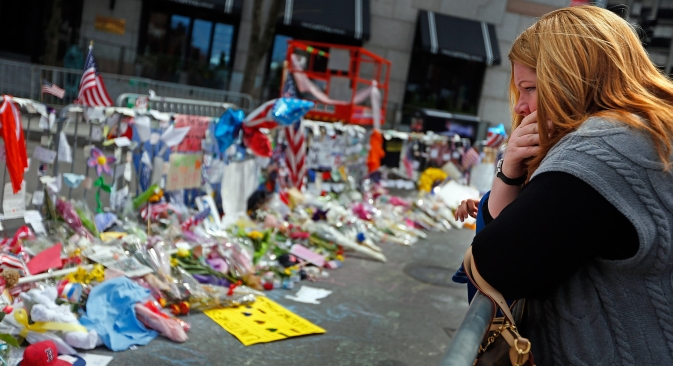 A woman looks over the memorial on Boylston Street Monday, April 22, 2013, in memory of the victims from the Boston Marathon bombing in Boston, Massachusetts. Source: Vostock Photo