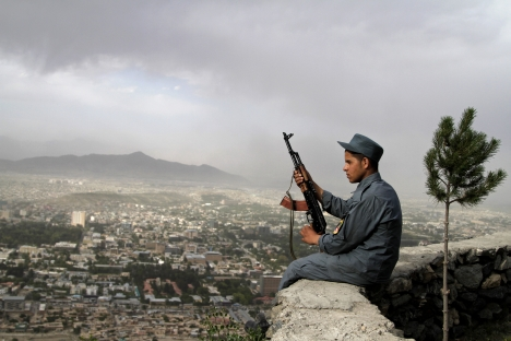 An Afghan policeman sits on a wall on a mountain overlooking Kabul, Afghanistan, Wednesday, May, 22, 2013. Source: AP
