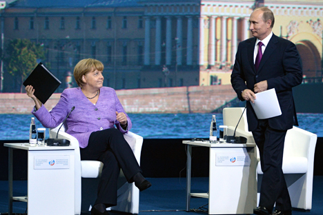 German Chancellor Angela Merkel and Russian President Vladimir Putin discussed the global economics in St. Petersburg. Source: Kommersant