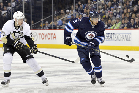 Winnipeg Jets' Evander Kane (R) tries to control a bouncing puck as he skates past Pittsburgh Penguins' Evgeni Malkin during the second period of their NHL hockey game in Winnipeg, on February 15. Source: Reuters / Fred Greenslade