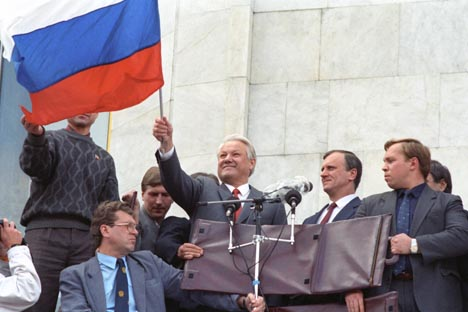 Russian President Boris Yeltsin (center) raising the Russian flag at a meeting as he stands outside the former Council of Ministers building on August 19, 1991. Source: ITAR-TASS