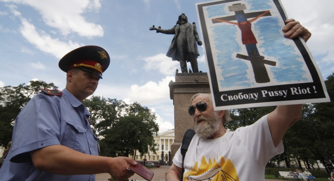 A police officer checks documents of participant in a rally in support of punk group Pussy Riot on Arts Square in St. Petersburg. Source: RIA Novosti / Vadim Zhernov