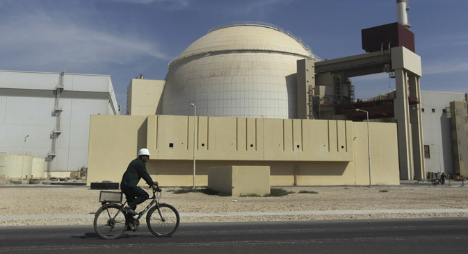 A worker rides a bike in front of the reactor building of the Bushehr nuclear power plant in Iran. Source: AP / Mehr News Agency / Majid Asgaripour