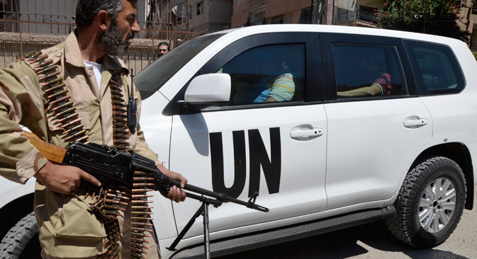 A Free Syrian Army fighter carries his weapon as he and fellow fighters escort a convoy of U.N. vehicles carrying a team of United Nations chemical weapons experts at one of the sites of an alleged chemical weapons attack in Damascus' suburbs of Zamalka, on August 28, 2013. Source: Reuters / Bassam Khabieh
