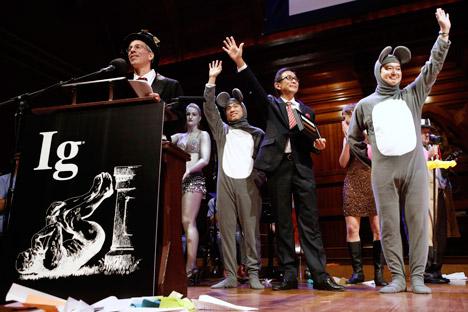 Master of ceremonies Marc Abrahams, left, introduces the winners of the Medicine Prize, Xiangyuan Jin, right mouse, of China, Masanori Niimi of Japan and Masateru Uchiyama of Japan during the annual Ig Nobel prize ceremony at Harvard University Thursday, Sept. 12, 2013 in Cambridge, Mass. Source: AP