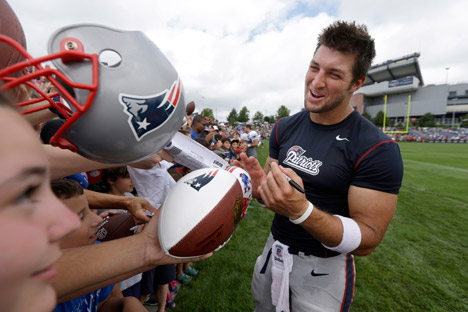 New England Patriots quarterback Tim Tebow, right, signs autographs for fans following an NFL football practice in Foxborough, July 28, 2013. Source: AP