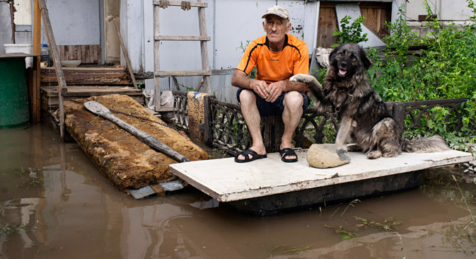 A man and his dog sit outside a house on a bank of the flooded Amur River, on the outskirts of Khabarovsk, Russia, Thursday, Aug. 22, 2013. The Russian Emergency Situations Ministry says around 20,000 people have been forced to leave their homes since July in the wake of floods in Russia's Far East. Source: AP