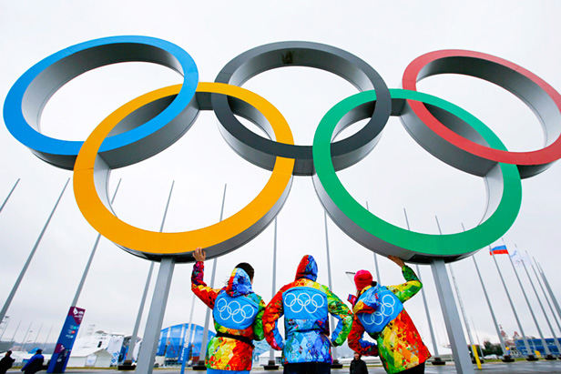 Volunteers stand on a platform displaying the Olympic rings on the Olympic Park as preparations continue for the Sochi 2014 Winter Olympics.