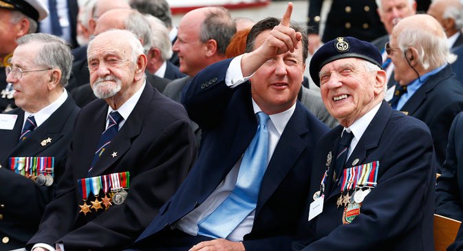 Britain's Prime Minister David Cameron points as he chats to D-Day veteran Kenneth Sturdy during an event on the deck of battleship HMS Belfast in central London, May 20, 2014. Source: Reuters